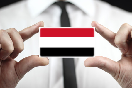 lag: Businessman holding a business card with Yemen Flag Stock Photo