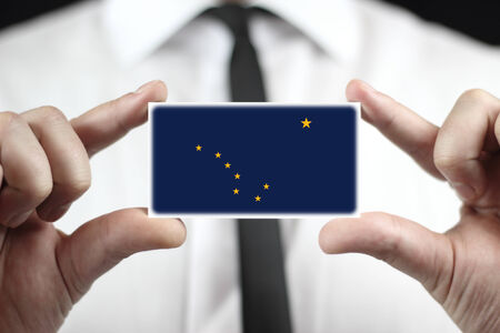 Businessman holding a business card with Alaska State Flag Stock Photo