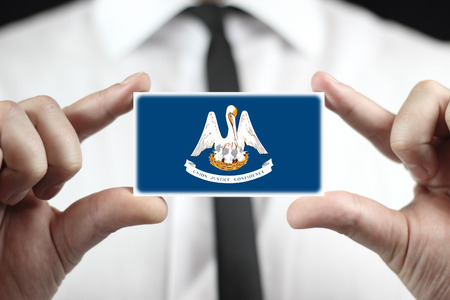 patiotic: Businessman holding a business card with Louisiana State Flag Stock Photo