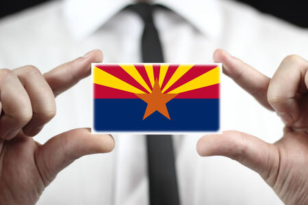 patiotic: Businessman holding a business card with Arizona State Flag