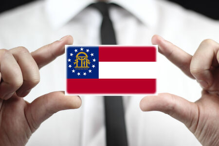 patiotic: Businessman holding a business card with Georgia State Flag Stock Photo