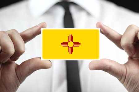 Businessman holding a business card with New Mexico State Flag
