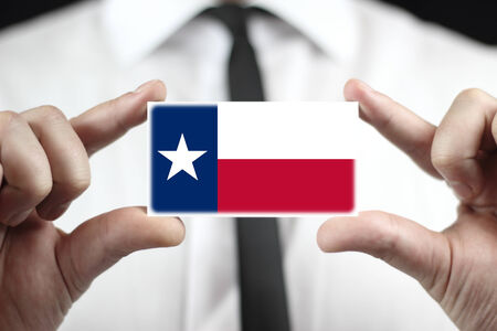 patiotic: Businessman holding a business card with Texas State Flag