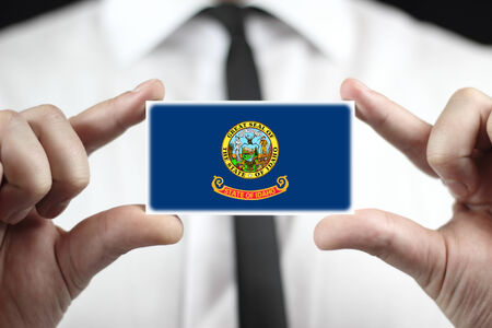 Businessman holding a business card with Idaho State Flag