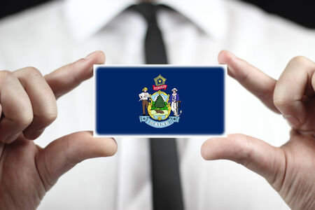 Businessman holding a business card with Maine State Flag