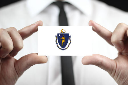 Businessman holding a business card with Massachusetts State Flag