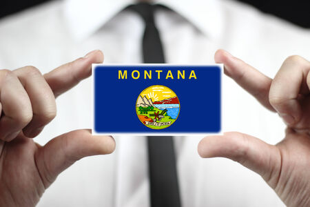 patiotic: Businessman holding a business card with Montana State Flag Stock Photo