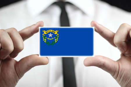 Businessman holding a business card with Nevada State Flag
