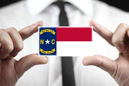 Businessman holding a business card with North Carolina State Flag