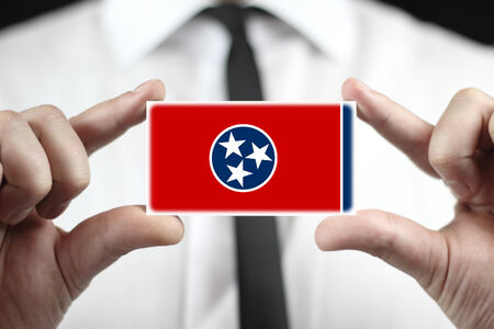 Businessman holding a business card with Tennessee State Flag