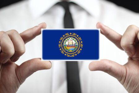 Businessman holding a business card with New Hampshire State Flag
