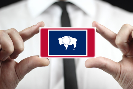 patiotic: Businessman holding a business card with Wyoming State Flag Stock Photo