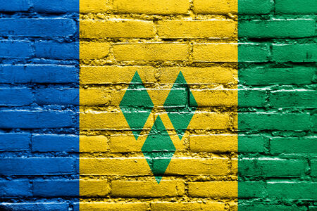 grenadines: Saint Vincent and The Grenadines Flag painted on brick wall Stock Photo