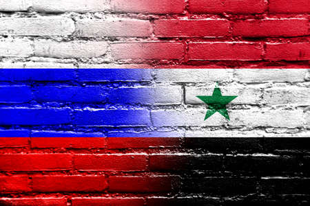 Russia and Syria Flag painted on brick wall photo