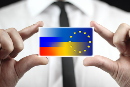 Businessman holding a business card with Ukraine, EU and Russia Flag photo