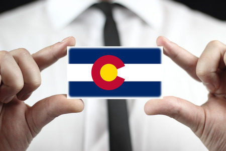 patiotic: Businessman holding business card with Colorado State Flag