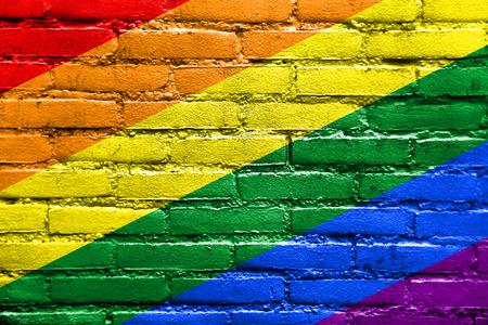identidad cultural: Bandera del arco iris pintado en la pared de ladrillo