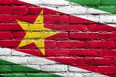 suriname: Suriname Flag painted on brick wall Stock Photo