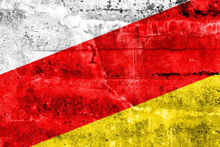 brick and mortar: South Ossetia Flag painted on grunge wall Stock Photo