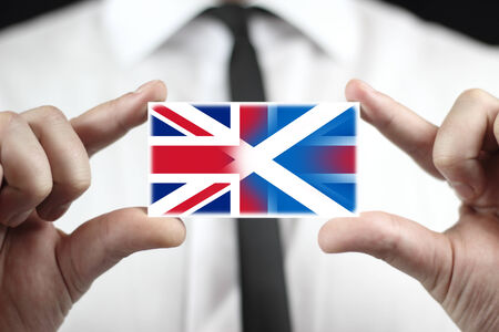 Businessman holding business card with Scotland and United Kingdom Flag photo