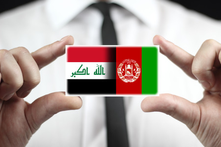 iraq money: Businessman holding a business card with Iraq and Afghanistan Flag