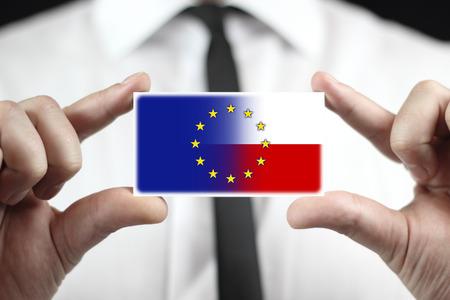 north atlantic treaty organization: Businessman holding a business card with Poland and European Union Flag