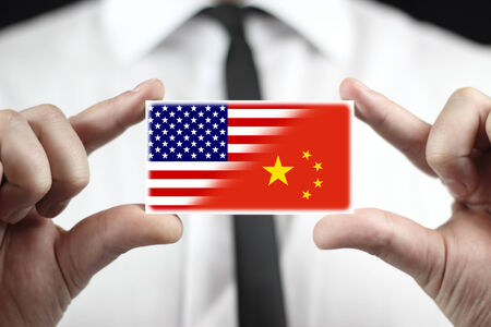 Businessman holding a business card with USA and China Flag photo