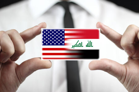 iraq money: Businessman holding a business card with USA and Iraq Flag