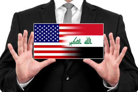 iraq conflict: Businessman holding a business card with USA and Iraq Flag