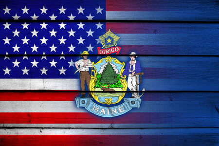 coupled: USA and Maine State Flag on wood background