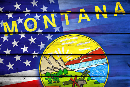consolidated: USA and Montana State Flag on wood background