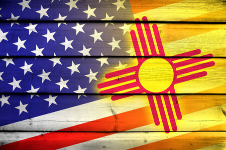 coupled: USA and New Mexico State Flag on wood background