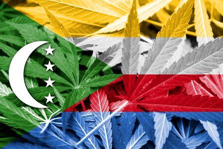 comoros: Comoros Flag on cannabis background. Drug policy. Legalization of marijuana Stock Photo