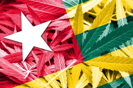 togo: Togo Flag on cannabis background. Drug policy. Legalization of marijuana Stock Photo