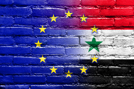 middle east crisis: EU and Syria Flag painted on brick wall