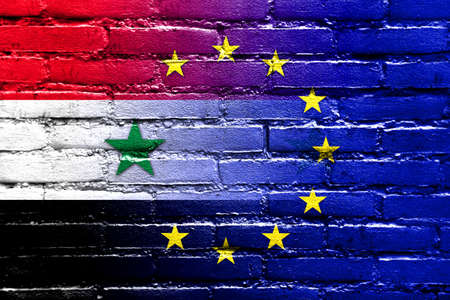 middle east crisis: European Union and Syria Flag painted on brick wall Stock Photo