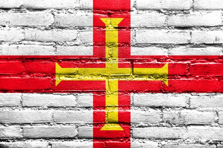 guernsey: Flag of Guernsey, painted on brick wall Stock Photo