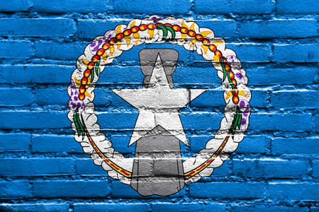 old flag: Flag of Northern Mariana Islands, painted on brick wall Stock Photo