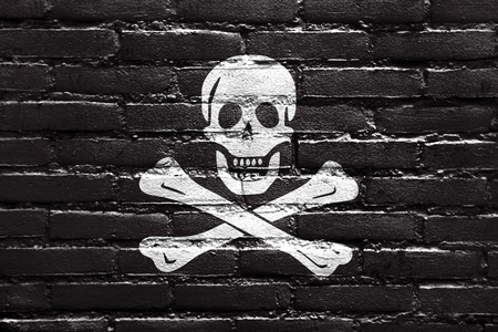 piracy: The traditional Jolly Roger of piracy Flag, painted on brick wall Stock Photo