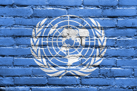 the united nations: Bandera de las Naciones Unidas, pintado en la pared de ladrillo