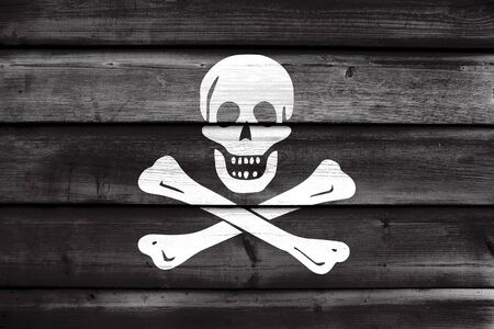 piracy: The traditional Jolly Roger of piracy Flag, painted on old wood plank background
