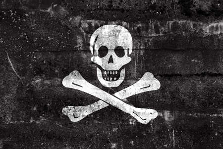 jolly roger: The traditional Jolly Roger of piracy Flag, painted on dirty wall. Vintage and old look.