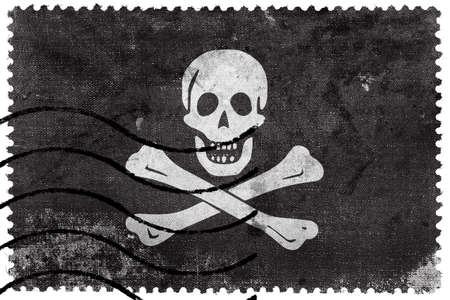 piracy: The traditional Jolly Roger of piracy Flag, old postage stamp Stock Photo