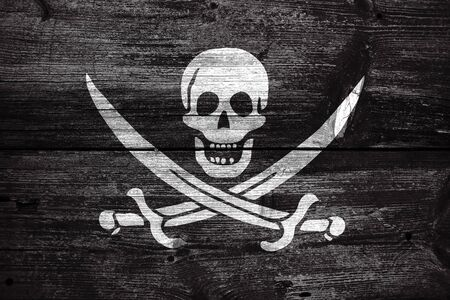 calico: Calico Jack Pirate Flag, painted on old wood plank background Stock Photo