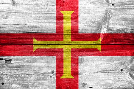 dependency: Flag of Guernsey, painted on old wood plank background