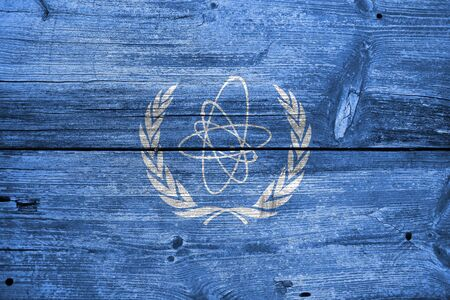 atomic energy: Flag of the International Atomic Energy Agency (IAEA), painted on old wood plank background