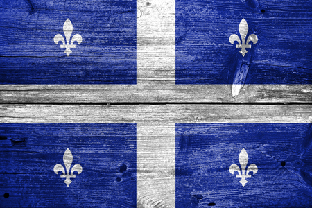quebec: Flag of Quebec, painted on old wood plank background Stock Photo