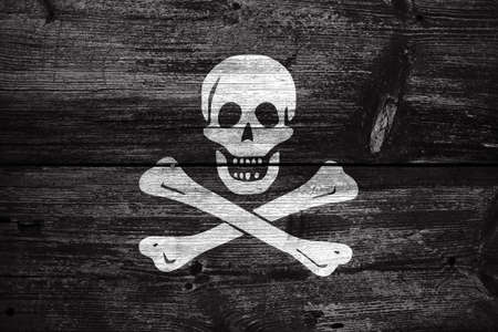 jolly roger: The traditional Jolly Roger of piracy Flag, painted on old wood plank background