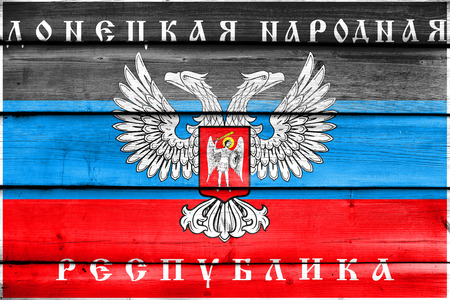 The flag of Donetsk Republic, a pro-Russian separatist organization operating in Donetsk, Ukraine, painted on old wood plank background