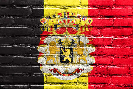 old flag: Flag of Belgium with Coat of Arms, painted on brick wall Stock Photo